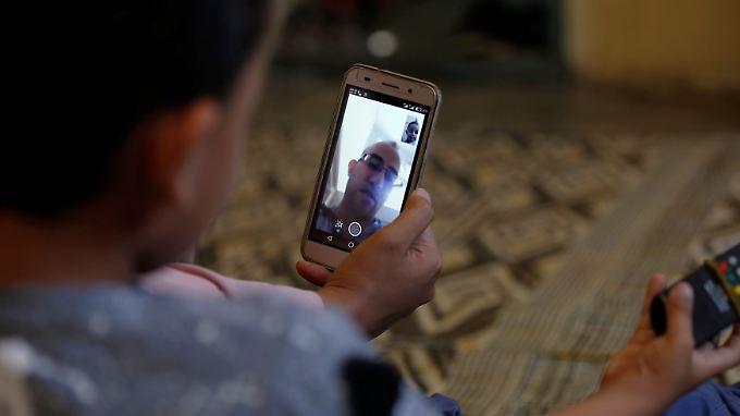 Ein Flüchtling blickt in einer Flüchtlingsunterkunft auf sein Handy. Wenn sich Migranten nicht ausweisen können, sollen ihre Smartphones dem Bamf dabei helfen, mehr über die Identität des Geflüchteten herauszufinden.