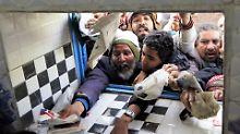 Menschen versammeln sich in Sanaa vor einem Fenster, um ihre täglichen Hilfsmittel von einem Lebensmittelverteilzentrum zu erhalten.
