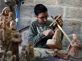 Ein palästinensischer Schnitzer fertigt in einer Werkstatt in Bethlehem Holzstatuen von Maria und Jesus.