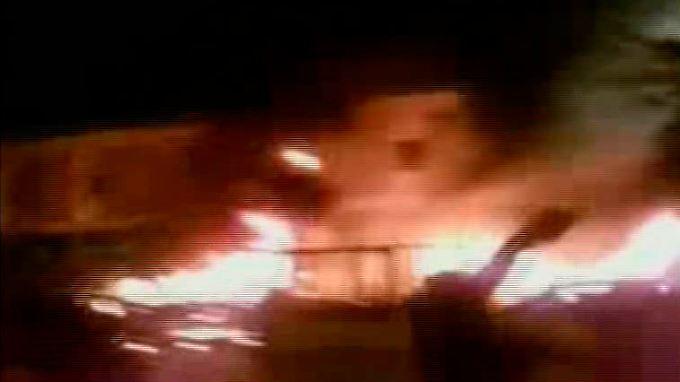 Mit Mobiltelefonen werden Fotos aufgenommen und im Internet verbreitet. Hier steht eine Polizeistation in Tripolis in Flammen.