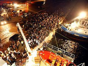 Im Hafen von Bengasi wollen Hunderte an Bord eines türkisches Schiffes.