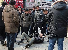 Zwischenfall in der Pekinger Fußgängerzone Wangfujing: Nicht identifizierte Männer in zivil umringen aus Sicherheitsgründen einen ausländischen Journalisten - nachdem sie ihn zu Boden gestoßen haben.