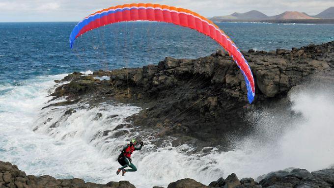 Der Extremsportler Mike Küng fliegt hier mit einem Gleitschirm an der Küste der spanischen Insel Lanzarote.