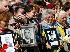 Frauen halten während einer Gedenkveranstaltung in Kiew Bilder ihrer Verwandten, die sie durch das Unglück in Tschernobyl verloren haben. (Archivbild vom 26.04.2010)