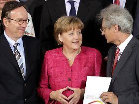 Standortpolitik im Jahr 2011: Angela Merkel eingerahmt von NPE-Leiter Henning Kagermann (rechts) und Autoverbandspräsident Matthias Wissman (links).