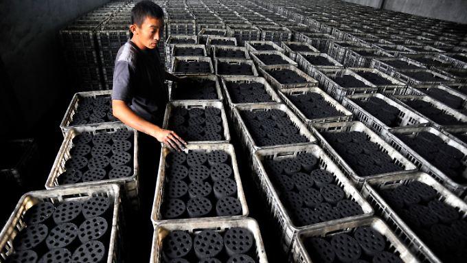 Ein Arbeiter stapelt in einer Fabrik in China Kohlebriketts. Mit dem Anstieg der Kohleverbrennung in China gelangen riesige Mengen Schwefeloxide in die Luft.