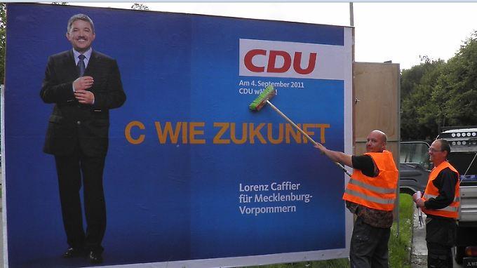 Für den Spruch, den sie plakatieren, können diese beiden Männer nun wirklich nichts.