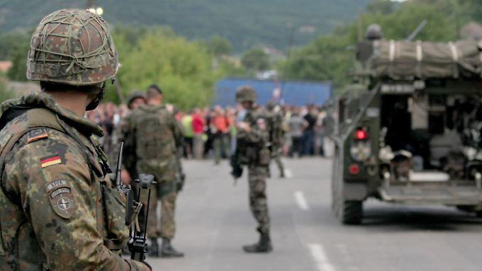 Ein Bundeswehrsoldat und slowenische KFOR-Soldaten vor einer Straßenblockade in Rudare.