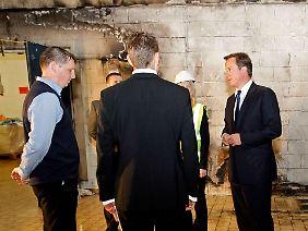 David Cameron, rechts, besichtigt ein beschädigtes Ladenlokal in London.