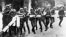 1. September 1939: Wehrmachtssoldaten öffnen einen Schlagbaum an der Grenze zu Polen.