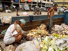 Die Armut ist bereits jetzt in vielen Ländern der Welt so groß (im Bild: Philippinen), dass Menschen im Müll nach Nahrung suchen.