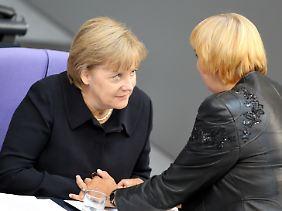 Merkel trug bei der Debatte im Bundestag schwarz. Am vergangenen Freitag war ihr Vater gestorben. Hier kondoliert Grünen-Chefin Claudia Roth.