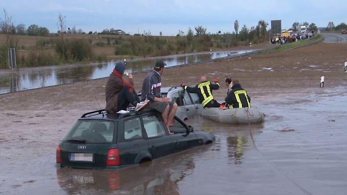Rettungskräfte befreien auf der A14 bei Plötzkau Insassen aus im Wasser stehenden Fahrzeugen.