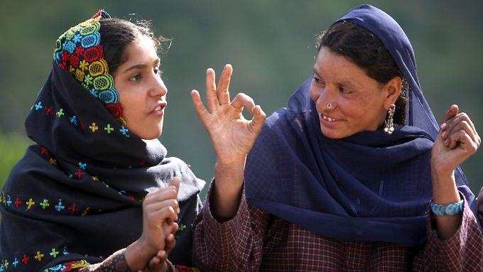Zwei gehörlose Frauen unterhalten sich mittels Gebärdensprache in Nordindien.