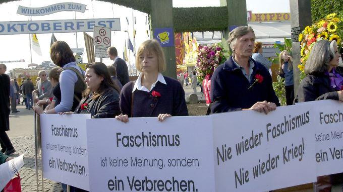 Demonstranten stehen am 20. Jahrestag des Anschlages vor dem Mahnmal am Haupteingang des Oktoberfestes.