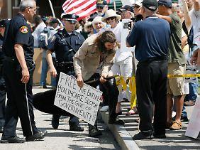 """... die Staatshasser sind draußen. Auf dem Plakat fordert der junge Mann, den gesamten Gesundheitsbereich """"von den Waffen des Staates"""" zu befreien."""