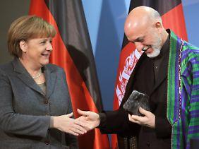 Für Merkel nimmt Karsai sogar sein Hütchen ab.