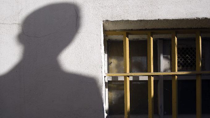 Der Schatten eines Mannes neben dem letzten erhaltenen Gitterfenster des ehemaligen Geschlossenen Jugendwerkhofes Torgau in der heutigen Gedenkstätte in Torgau. Dieser Jugendwerkhof wurde in der DDR von 1964 bis 1989 als Geschlossener Jugendwerkhof genutzt.
