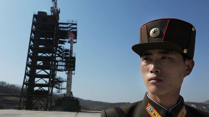 Ein nordkoreanischer Soldat steht vor einer Abschussrampe mit einer Unha-3-Rakete.