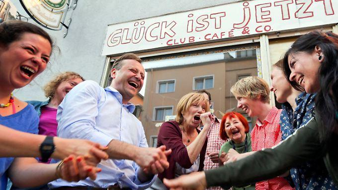 """Laurenz Menzing (3.v.l.) und die Mitglieder vom LachClub """"Glück-ist-jetzt""""  vor dem kleinen Ladenlokal in Frankfurt am Main."""