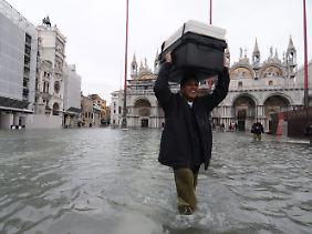 Mit einem Lächeln auf den Lippen trägt dieser Bürger seinen Koffer über den Markusplatz.