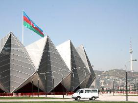 An der Crystal Hall in Baku weht die aserbaidschanische Nationalflagge, rechts ist der Fernsehturm zu sehen.