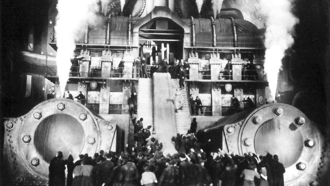 """Eine aufgebrachte Menschenmenge steht vor einem dampfenden Maschinengebäude, eine Szene aus dem Stummfilmklassiger """"Metropolis""""."""