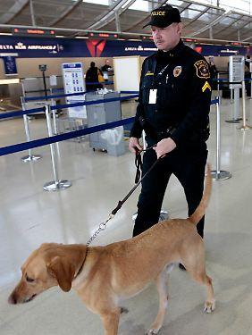 Ein Sicherheitsbeamter am Flughafen von Detroit patroulliert mit seinem Hund.
