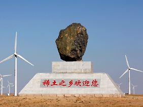 """Symbol der Kontrolle: Über einer Lagerstätte in der Inneren Mongolei thront dieser Markstein mit der Inschrift """"Willkommen in der Heimat der Seltenen Erden""""."""