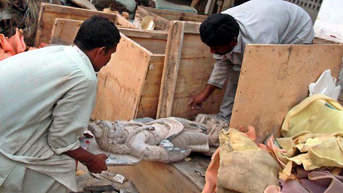 Pakistanische Polizisten öffnen Truhen mit historischen Skulpturen, die zuvor bei einem Kunstraub gestohlen worden waren.