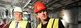 Bauleiter Korkhaus (l.) zeigt Delius, wie die Anlagen zur Entrauchung, Belüftung und Klimatisierung arbeiten.