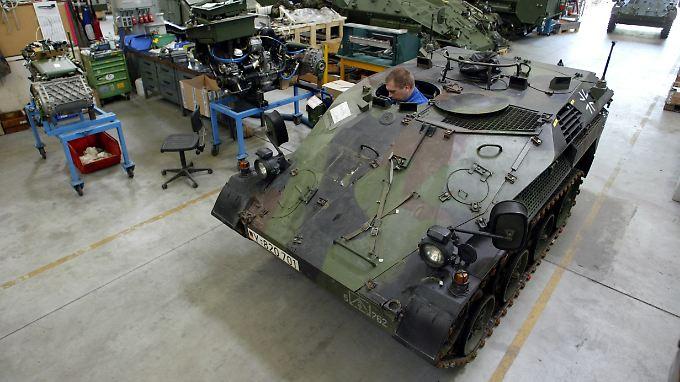 """Ein Rheinmetall-Mitarbeiter arbeitet in einem """"Wiesel""""."""