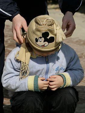 Der Vater eines autistischen Jungen versucht ihn zum Gehen zu motivieren.