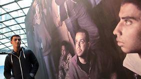 Der junge Fotojournalist Jonathan Rashad neben einem Bild der Revolution in Kairo.