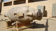 Der Kopf gehört zu einer Figur, die den Pharao sitzend mit vor der Brust verschränkten Armen zeigt.