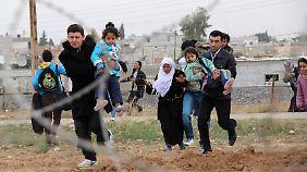 Syrer rennen über die Grenze in die Türkei in Richtung der Stadt Ceylanpinar.