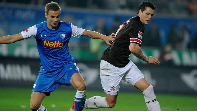 Holmar Örn Eyjolfsson (l.) und St. Paulis Daniel Ginczek bei der Rasenschlacht um den Ball.