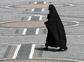 Eine Frau in einer Burka geht über den Odeonsplatz in München.