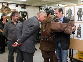 """Peter Jackson (l.) führte Prinz Charles bei dessen Besuch in seiner Firma für filmische Spezialeffekte namens Weta durch sein Reich. Rechts der Bifur-Darsteller William Kircher aus """"Der Hobbit""""."""