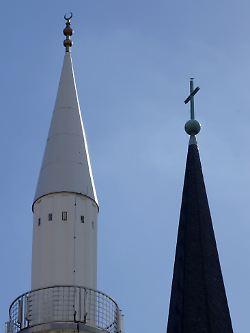 Die Spitze des Minarett der Yavus Sultan Selim Moschee (l.) mit dem Halbmond und das Kreuz auf der Kirchturmspitze der Liebfrauenkirche in Mannheim.
