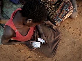 Alice Amito sitzt mit Epilepsie-Tabletten in den Händen vor einer Hütte im Kitgum Distrikt in Norduganda. Sie leidet am Kopfnicken-Syndrom.