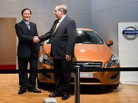 Geely-Chef und –Haupteigner Li Shufu und Fords Finanzchef Lewis Booth schütteln sich in der Volvo-Zentrale in Göteborg die Hände.