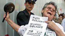 """Mit einem Plakat mit der Aufschrift """"Ich habe Dollar eingezahlt, ich will Dollar wiederhaben"""" protestiert eine Frau im Februar 2002 vor der Citibank in Buenos Aires."""