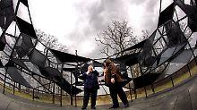 Besucher der Pfaueninsel in Berlin betrachten einen begehbaren Pavillon aus Glas und Stahl, ...