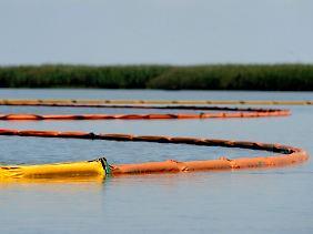 Schwimmende Barrieren sollen verhindern, dass das Öl das Marschland erreicht. Mit einer Kuppel will BP das Bohrloch abdichten.