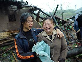 Zwei Frauen stehen vor den Trümmern eines Hauses.