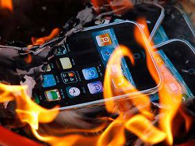 Demonstranten verbrennen symbolisch Papier mit dem Aufdruck des Displays eines iPhones.