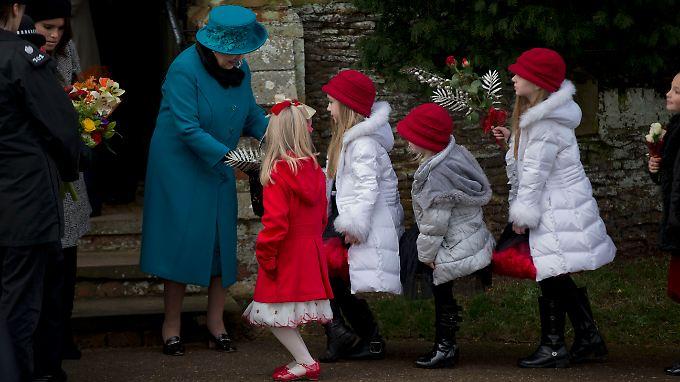 Mit Knicks: Königin Elizabeth II. wird nach der Messe in Sandringham von Kindern mit Blumen begrüßt.