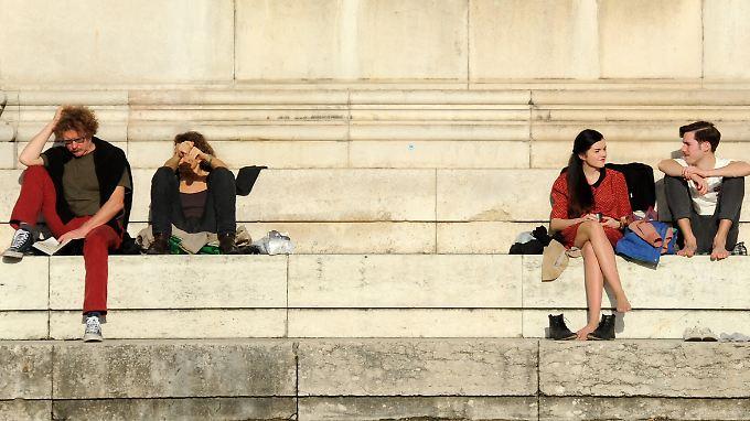 Wärmer als an manchem Sommertag 2012: Menschen sitzen in München auf den Stufen der Glyptothek am Königsplatz in der Sonne.