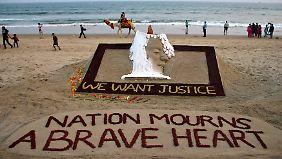 """""""Wir wollen Gerechtigkeit"""" steht unter einer Sandskulptur des indischen Künstlers Sudarshan Patnaik."""